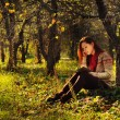 Young woman with long red hair reading under the tree — Stock Photo #55712633