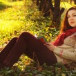 Young woman with long red hair reading under the tree — Stock Photo #55712681
