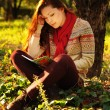 Young woman with long red hair reading under the tree — Stock Photo #55712731