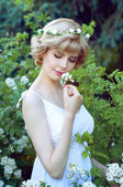 Beautiful blonde woman in white sundress posing in garden — Stock Photo