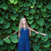 Blonde caucasian woman lost among ivy leaves — Stock Photo