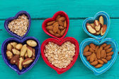 Ceramic heart shape bowls with healthy breakfast items: whole oatmeal, almonds and Brazil nuts — Stock Photo