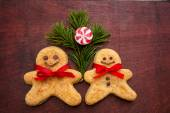 Gingerbread cookie man, candy ,fir branches on the old wooden board — Stock Photo