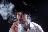 Handsome man holding cigar with smoke — Stock Photo