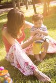 Mother play with her son in the park with a warm filter applied — Stock Photo