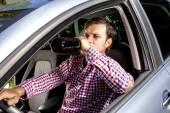 Joven businesssman beber alcohol mientras se conduce — Foto de Stock