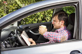 Young man reading and drinking coffee while driving — Stock Photo