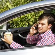 Young man speaking on phone and drinking coffee while driving — Stock Photo #59318589