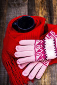 Cup of hot drink wrapped by red scarf and gloves on wooden board — Stock Photo