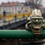 Постер, плакат: Little gnome statue on the bridge in the rain