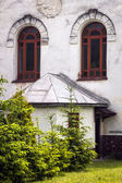 Windows of white Catholic Church in Slovakia close to firs — Stock Photo