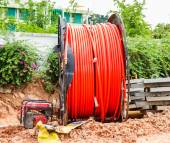 Spool of cable and fiber optics in the road. — Stock Photo
