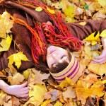 Girl lying in autumn leaves portrait. — Stock Photo #51875639