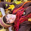 Happy girl in knitted hat lying in autumn leaves. — Stock Photo #51875645