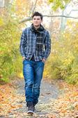 Smiling man walking in autumn park. — Stock Photo
