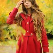 Young fashion woman dressed in red coat in autumn park. — Stock Photo #56717199