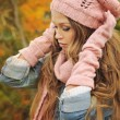 Woman dressed in pink knitted hat, scarf and gloves in autumn park. — Stock Photo #56717373