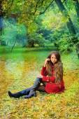 Woman in red sitting in autumn park. — Stock Photo