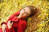 Smiling woman in red coat lying in autumn leaves in park. — Stock Photo