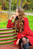 Woman dressed in red coat sitting in autumn park. — Foto de Stock