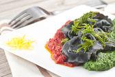 Black ravioli with spinach and garlic sauce tomato. — Stock Photo