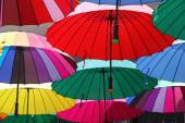Collection of multi colored umbrellas hanging up. — Stockfoto
