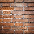 Red brick background: closeup of an old uneven brick wall. — Stock Photo #66874069