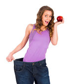 Woman with huge trousers holding apple — Stock Photo