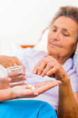Elderly woman taking pills — Stock fotografie