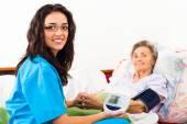 Nurse measuring elderly patient's blood pressure — Stock Photo