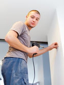 Electrician with solder iron on ladder working — Stock Photo