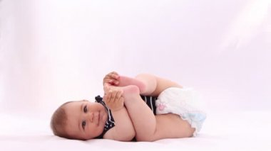 Little baby boy playing with his feet against white background — Stock Video