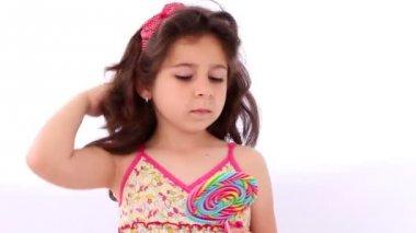 Little girl using a lollipop as a mirror, straighten her hair — Stock Video