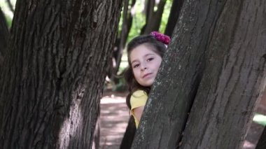 Girl hiding behind a tree — Stock Video