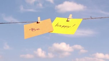 """Sentence """"be happy"""" on colorful paper pinched on a rope. Positive thinking concept — Stock Video"""