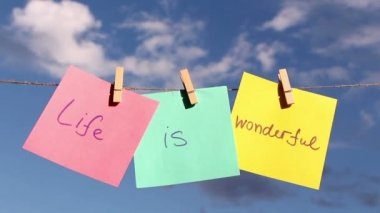 """Sentence """"Life Is Wonderful"""" on colorful paper pinched on a rope. Positive thinking concept — Стоковое видео"""