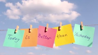 """Sentence """"Today Is Better Then Yesterday"""" on colorful paper pinched on a rope. Positive thinking concept — Stock Video"""