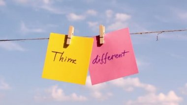 """Sentence """"Think Different"""" on colorful paper pinched on a rope. Positive thinking concept — Stock Video"""