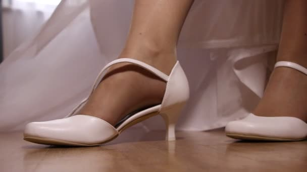 Novia en vestido de Novia de poner en sus zapatos blancos, closeup — Vídeo de stock