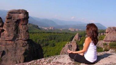 Woman doing yoga exercises on Belogradchik rocks, admiring the Belogradchik valley — Stock Video