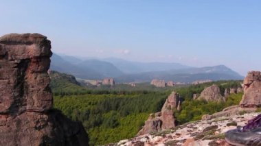 Women feet in sport shoes step on a rock, tourist admire the Belogradchik valley — Stock Video