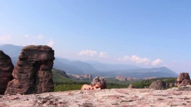 Man is climbing a rock and sitting to admire the beautiful Belogradchik valley — Stock Video