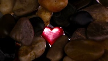 Red crystal heart among stones — Stock Video