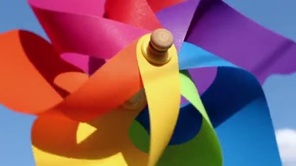 Juguete de pinwheel colorido contra el cielo azul — Vídeo de stock