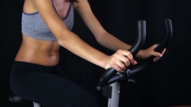Close up of a young woman riding stationary bike — Stock Video
