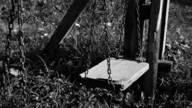 Black and white video of empty broken swing, concept of abandoned child — Stockvideo