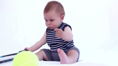Happy baby boy is playing with tennis racket on a white background — Stock Video