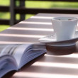 Blinds on pavilion throw shadow over a table with magazine and coffee cup — Stock Video #61286485