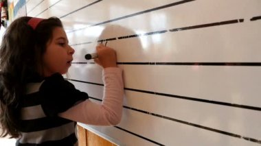 Girl writing mathematic expression on the blackboard in a classroom — Stok video