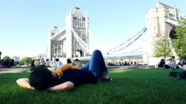 Woman is laying on a lawn by Tower Bridge, time lapse of people moving along the Thames path — Stock Video